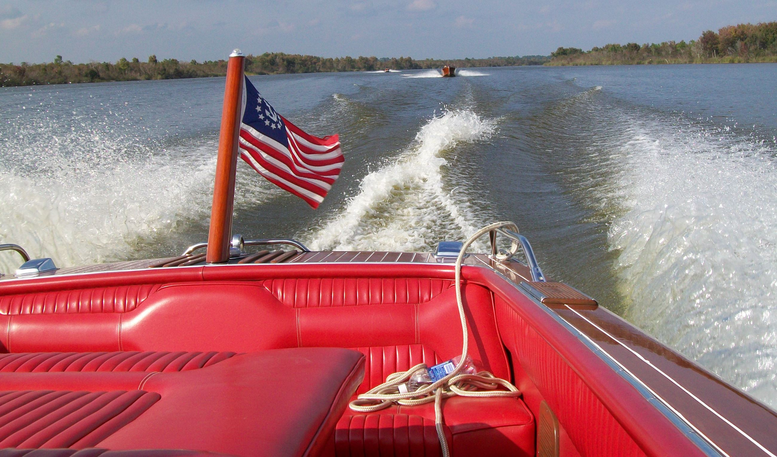 Image of Antique Boat and American Flag Boating in Lake Dora